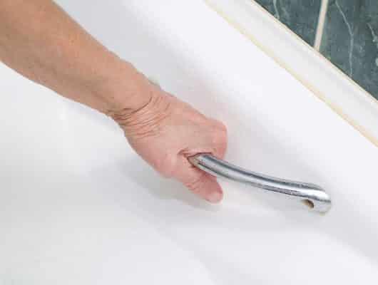 personne âgée prend bain et s'appuie sur barre de soutien
